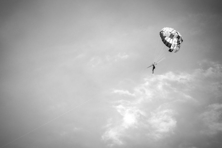 Low angle view of man parasailing against sky