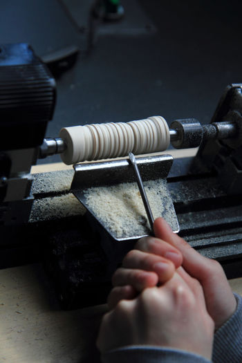 High angle view of cropped hands cutting wood