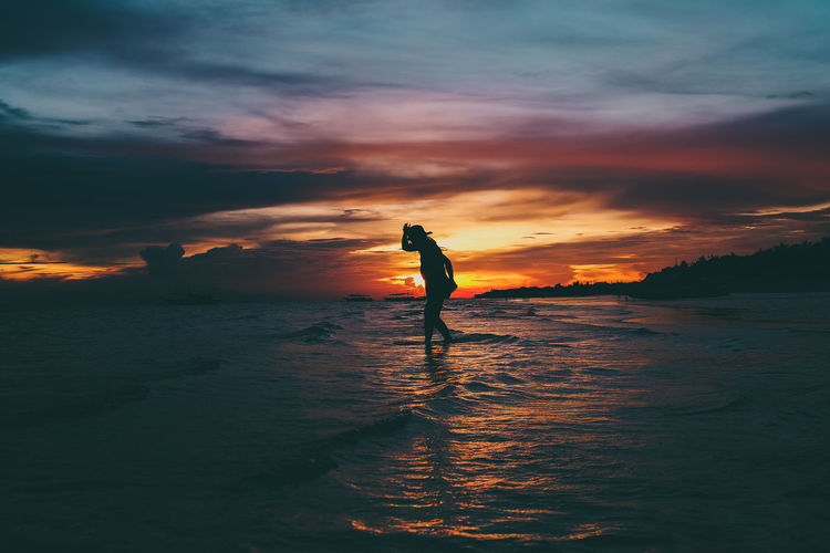 Silhouette woman wading in sea against sky during sunset