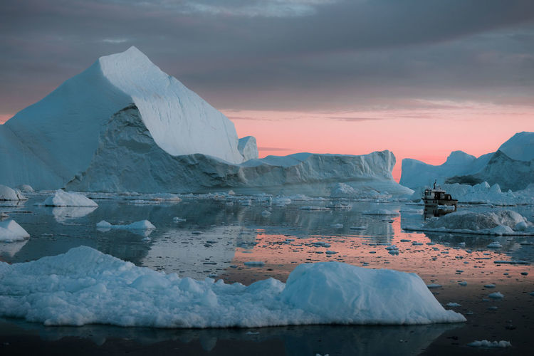 """Icebergs in a sunset depicting the color pantone of the year """"living coral"""" Cold Temperature Water Ice Winter Glacier Frozen Snow Scenics - Nature Beauty In Nature Sky Tranquil Scene Tranquility Iceberg Landscape Environment Sea Iceberg - Ice Formation Nature No People Floating On Water Outdoors Snowcapped Mountain Melting Boat"""