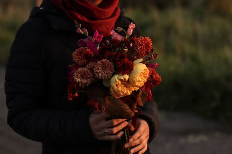 Midsection of person holding rose bouquet