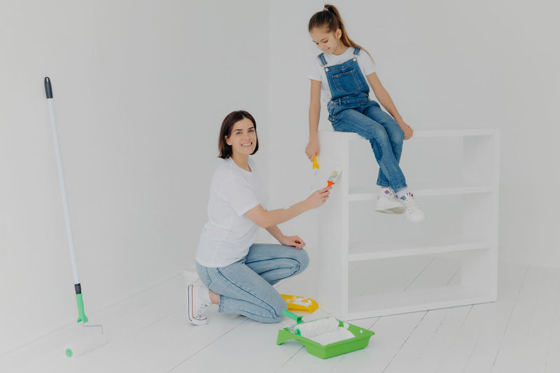 Full length of mother and daughter holding paint roller sitting at home