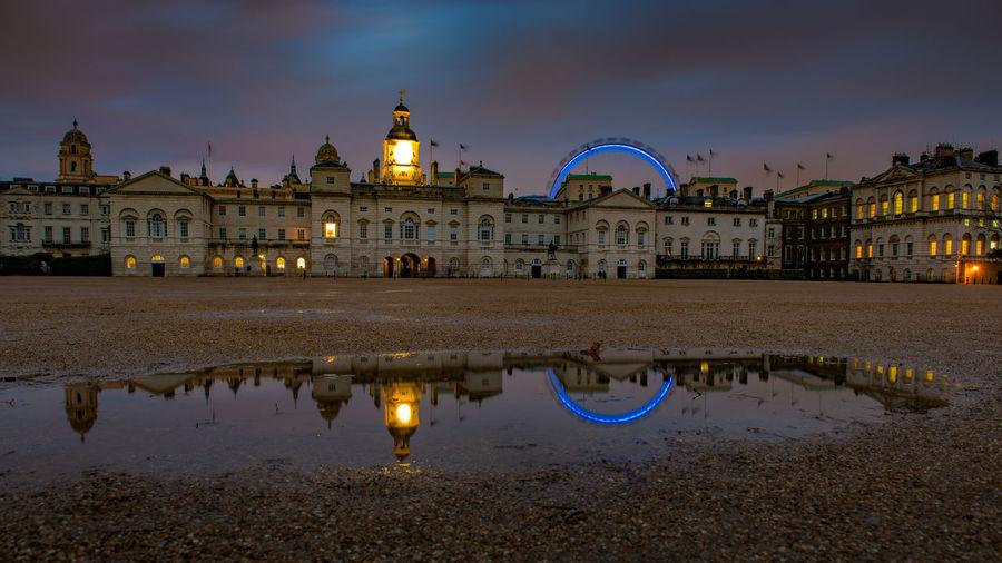 Illuminated London Eye By Palace Of Whitehall Against Sky At Night