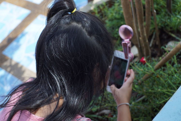 Four-year-old girl is intending to shoot with a mobile camera. Going Remote Thai Thai Girl Thailand Activity Adult Black Hair Child Day Focus On Foreground Hair Hairstyle Headshot Holding Leisure Activity Lifestyles One Person Outdoors Photography Themes Portrait Real People Rear View Technology Women The Fashion Photographer - 2018 EyeEm Awards The Still Life Photographer - 2018 EyeEm Awards