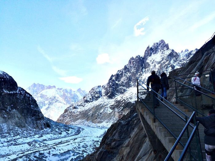 Low Angle View Of People On Staircase By Snowcapped Mountain Against Sky