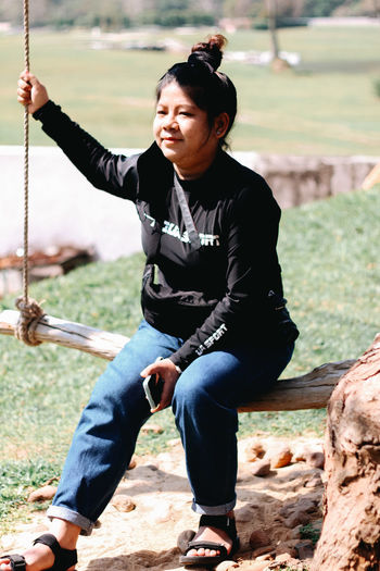Full length of woman sitting on swing at playground