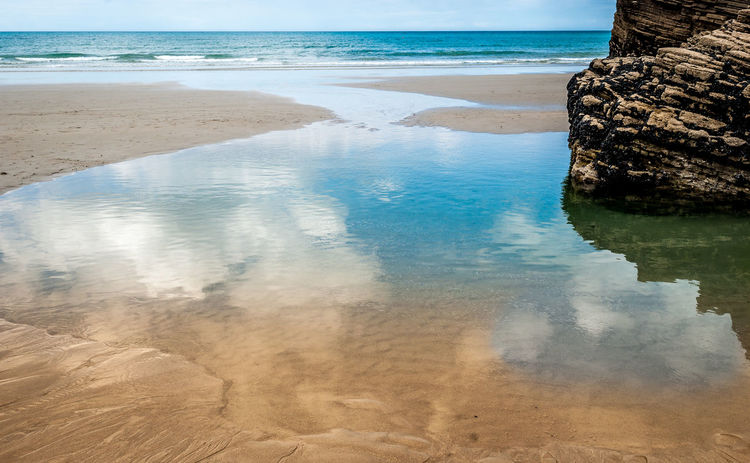 Tropical sandy beach with clear sky at the low tide. Cathedrals beach (playa de las catedrales) Spain Atlantic Atlantic Ocean Cathedrals Beach Galicia, Spain Playa De Las Catedrales Galicia Playa De Las Catedrales Praia Reflection Rock SPAIN Beach Beauty In Nature Catedrales Day Island Nature No People Ocean Outdoors Scenics Sky Water Waterfront
