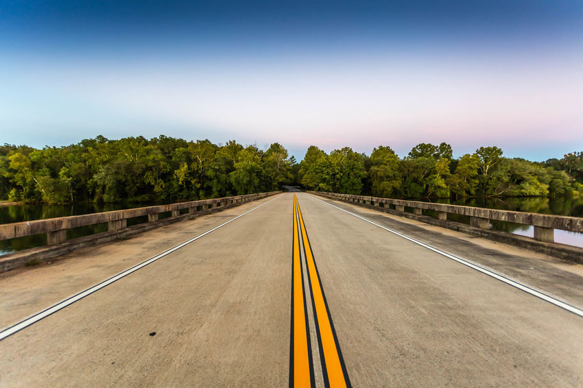Bridge Over Ocmulgee River Blue Clear Sky Copy Space Country Road Countryside Day Diminishing Perspective Double Yellow Line Empty Green Landscape Long Nature Outdoors Road Road Marking Solitude Surface Level The Way Forward Tranquil Scene Tranquility Transportation Tree Vanishing Point Yellow Line