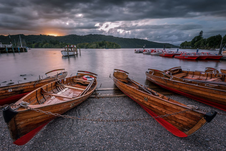 Boats moored in sea against cloudy sky