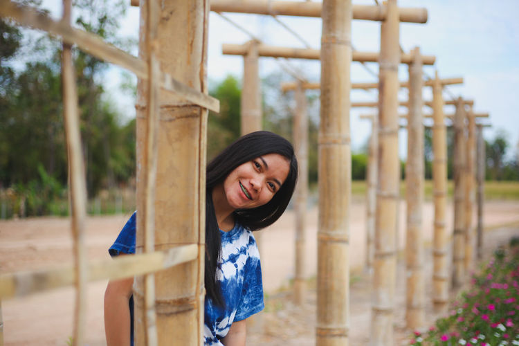 Portrait of smiling young woman by bamboo built structure
