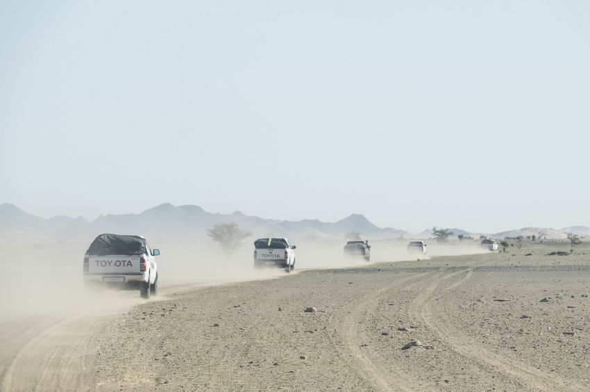 column of off road trucks running through the Sahara desert with dust behind Tourism Destination Destination Road Trip Off Road Gravel Path Sahara Desert Dust Adventure Caravan Mode Of Transportation Transportation Land Vehicle Sky Copy Space Landscape Environment Nature Day Motor Vehicle Land Road No People Scenics - Nature Clear Sky Truck Outdoors