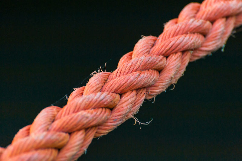 Close-up of rope tied against black background