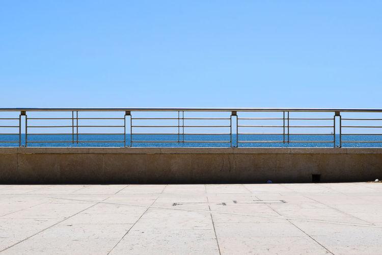 Empty pedestrian zone by sea against clear blue sky