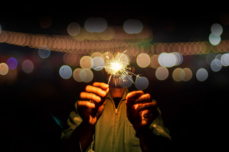 Midsection Of Man Holding Illuminated Sparklers At Night