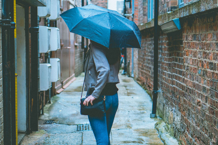 Woman Holding Umbrella While Walking On Street Amidst Buildings