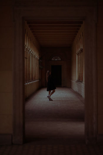 Full length of young woman standing in dark corridor