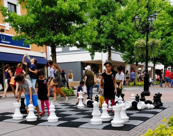 Chaos on the street Mobile Photography Street Chess Shopping Mall Street Photography People Children Girl Sunshine Summer Warm Day Tree Chess Pawn - Chess Piece Queen - Chess Piece Leisure Games King - Chess Piece Knight - Chess Piece Board Game Chess Piece Chess Board