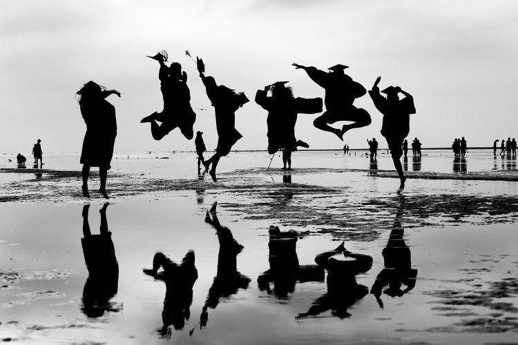 Silhouette People Jumping At Beach Against Sky