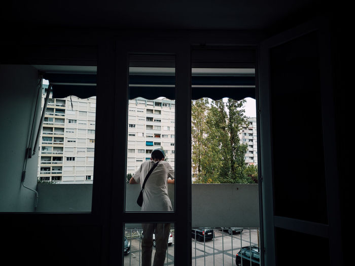Rear view of man standing by window in building