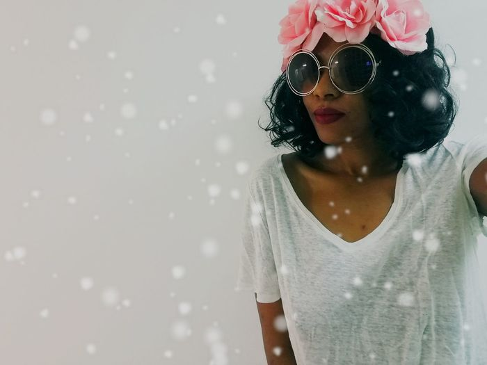 Portrait of woman wearing sunglasses and tiara during snowfall