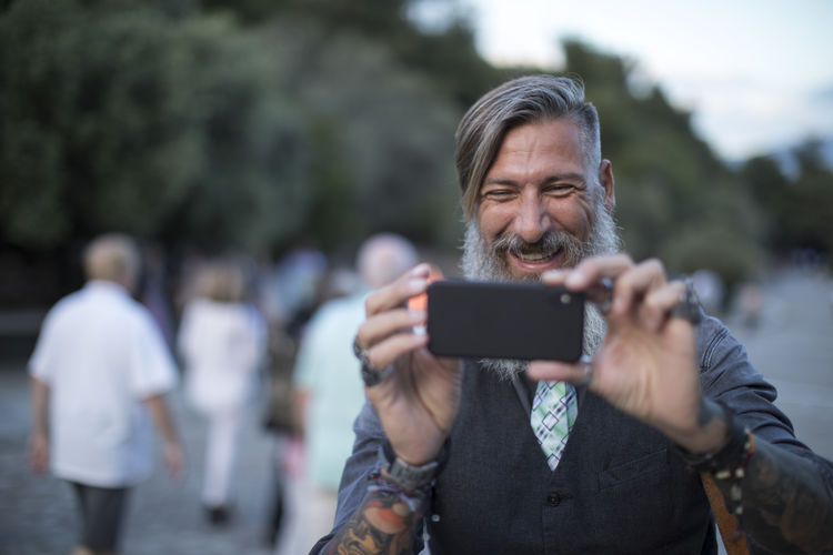 Happy Mature Man Photographing With Mobile Phone While Standing Outdoors