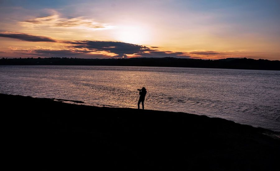 Sunset Silhouette Beauty In Nature Scenics Nature Tranquility Tranquil Scene Water One Person Sky Standing Outdoors Full Length Sea Beach Real People Men One Man Only People Taking Photos Cotswolds