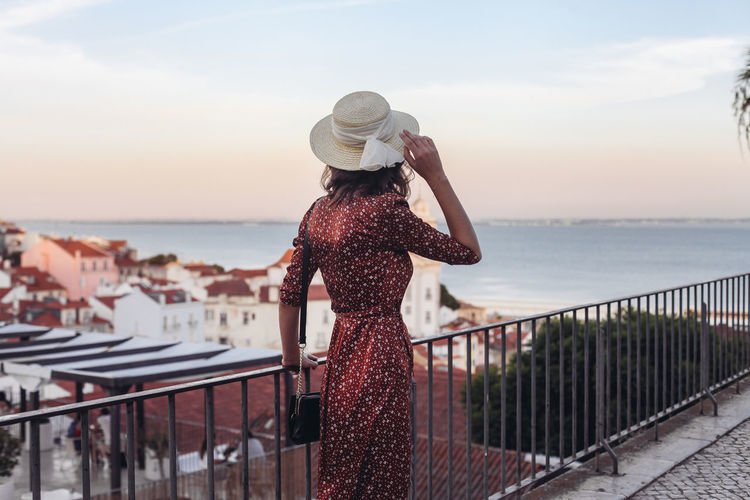 Woman standing by railing against sea