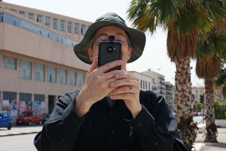 Man photographing with mobile phone while standing in city