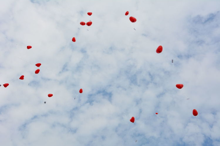 Low angle view of red heart shaped helium balloons flying in cloudy sky