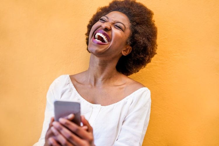 Young black woman standing isolated over yellow background using smart mobile phone African Afro Cellphone Fashion Happy Laughing Woman Young Adult Cell Communication Device Girl Hair Hairstyle Happiness Media Online  Phone Portrait Smartphone Smiling Technology Trendy Yellow
