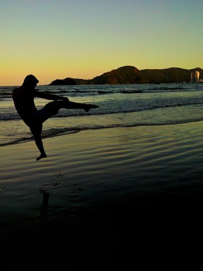 Silhouette man on beach against clear sky during sunset