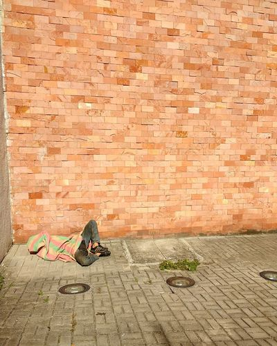 Homeless person lying on footpath by brick wall