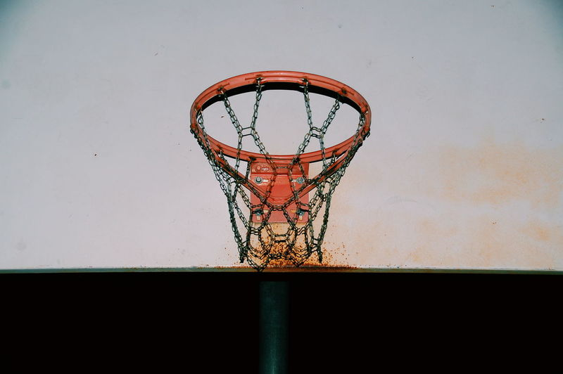 Low angle view of rusty basketball hoop at night