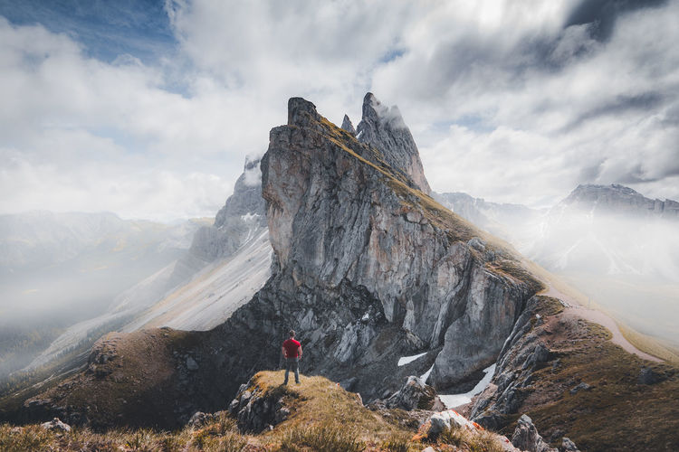 People on rocks by mountain against sky