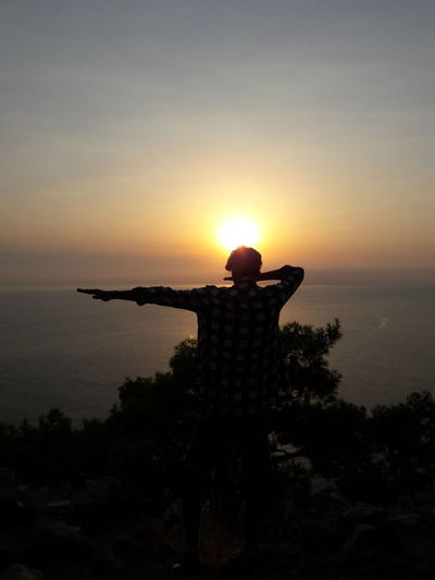 Rear view of silhouette man standing by sea against sky during sunset