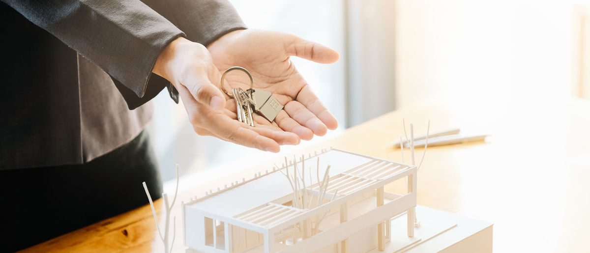 Midsection of real estate agent holding key by model house