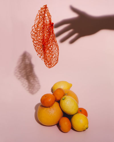 Still life with citrus fruits, orange net floating and the shadow of a hand on a pink background