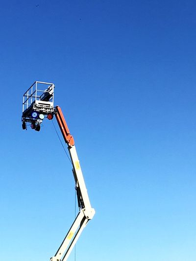 Low angle view of cherry picker against clear blue sky
