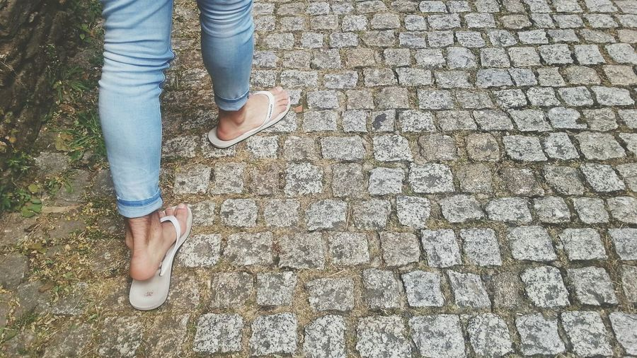 Low section of woman wearing flip-flops