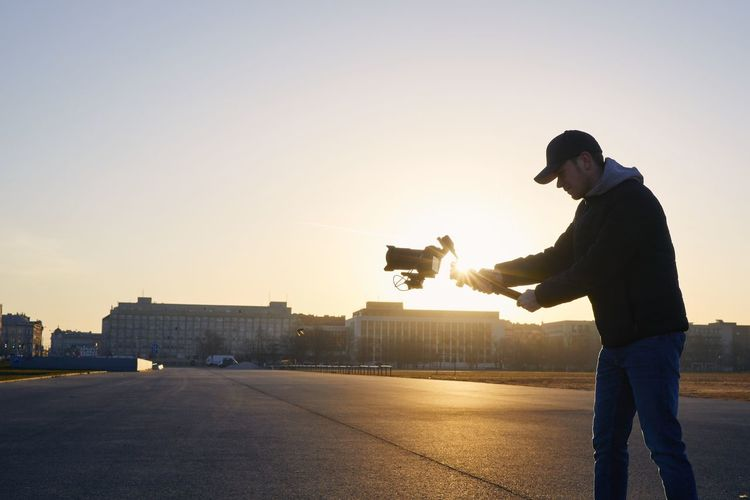 Side view of young man photographing at sunset