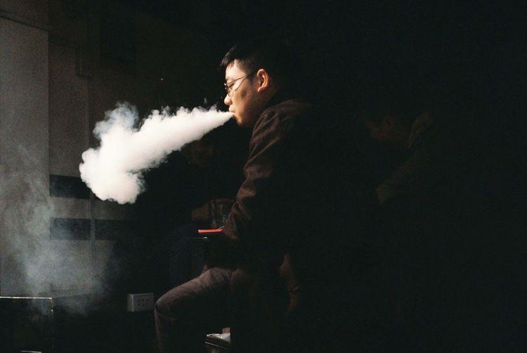 Man exhaling smoke while sitting in darkroom