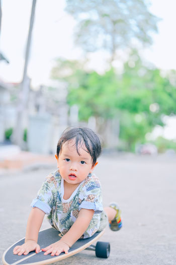 Portrait of cute boy sitting outdoors