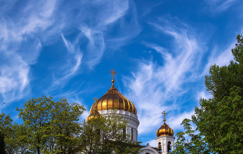 Golden cupola of moscow orthodox cathedral under cloudy blue sky