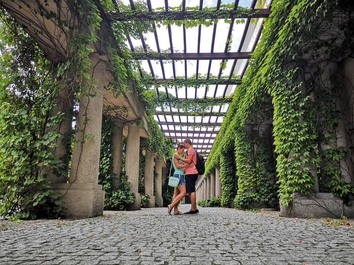 Side View Of Young Couple Standing By Plants And Columns In Park