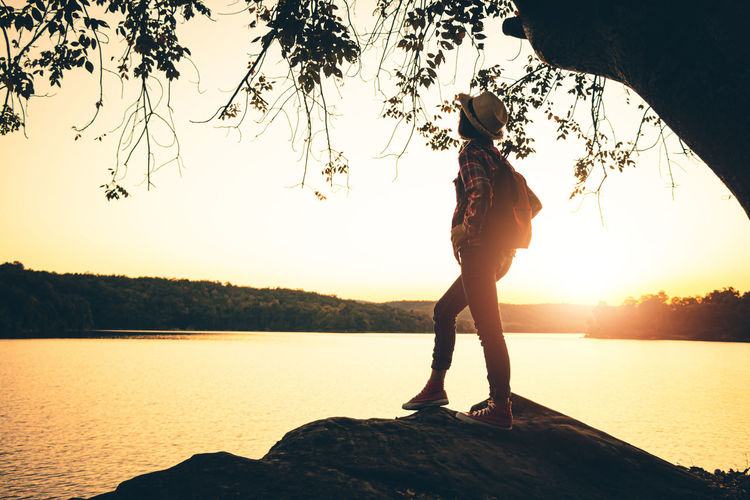 Silhouette woman standing by lake against sky during sunset