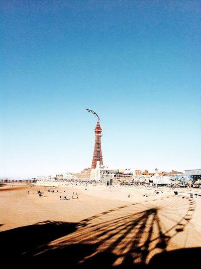 Shadow Of Ferris Wheel At Beach In City Against Clear Blue Sky