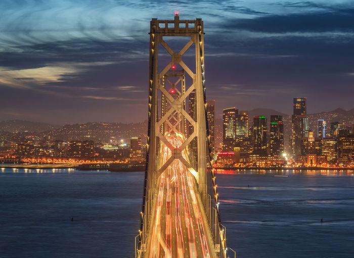 Illuminated bridge over river in city against sky at night