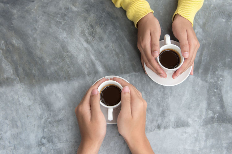 Directly above shot of hand holding coffee cup