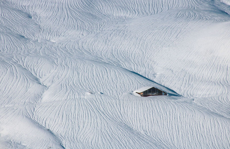 High angle view of snow and chalet on land