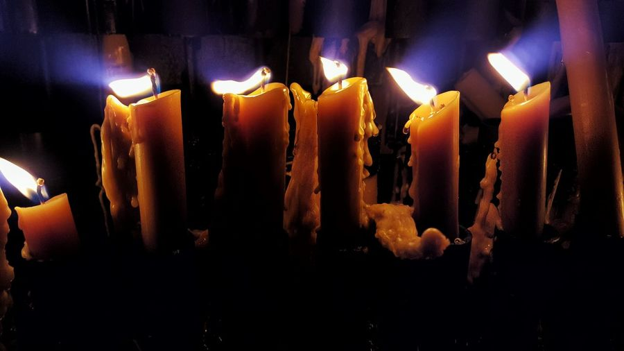 Close-up of lit candles in darkroom